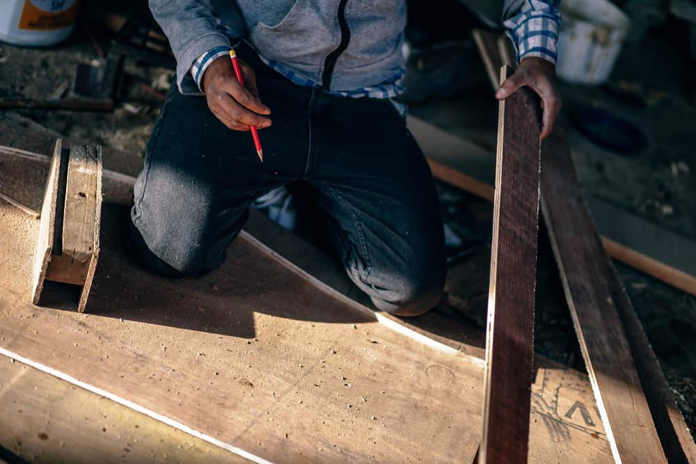 builder measuring out wooden slats milton keynes